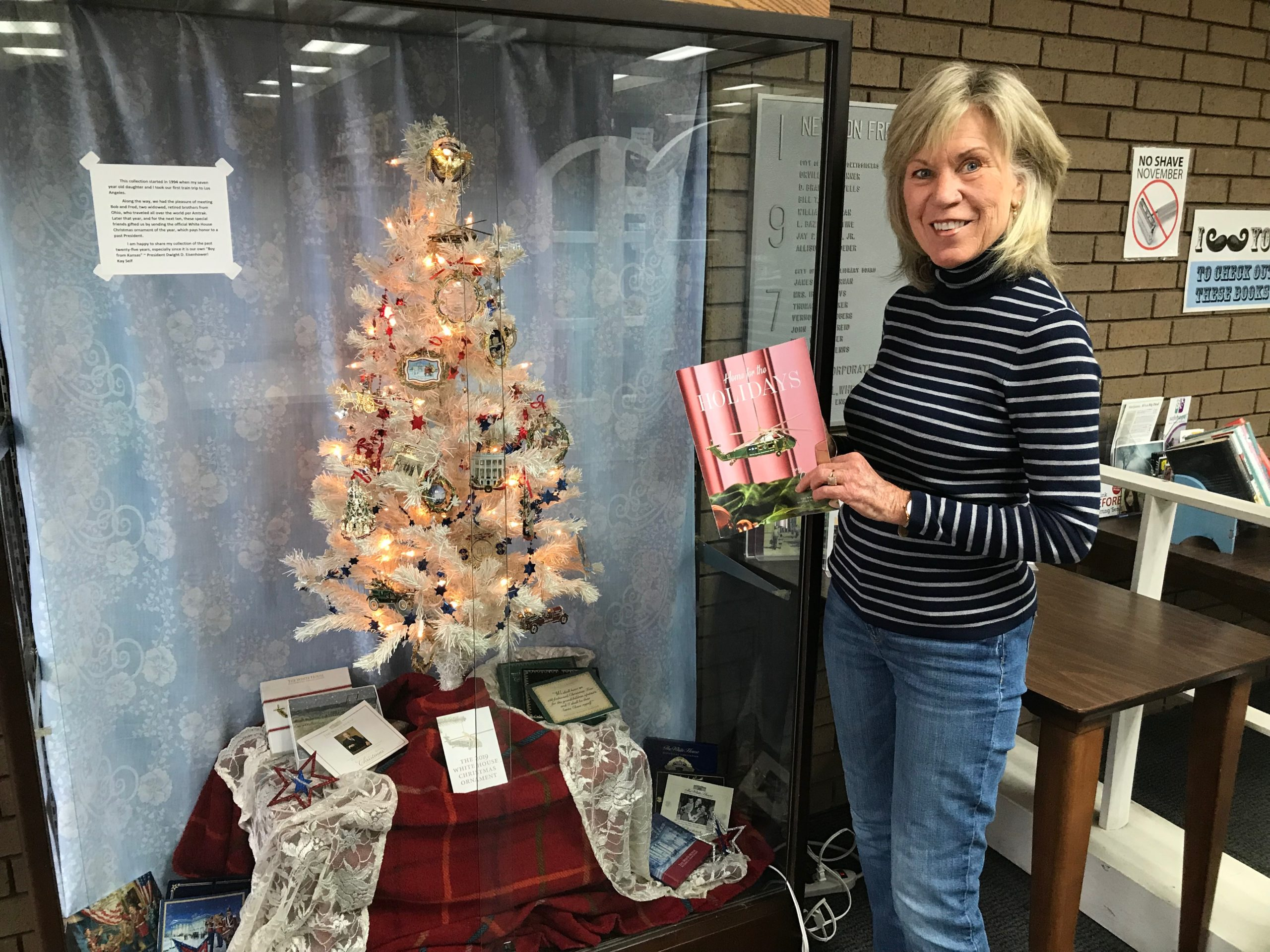 Kay Self poses for a photo with her Christmas ornament display. White House commemorative Christmas ornaments on a white artificial tree.