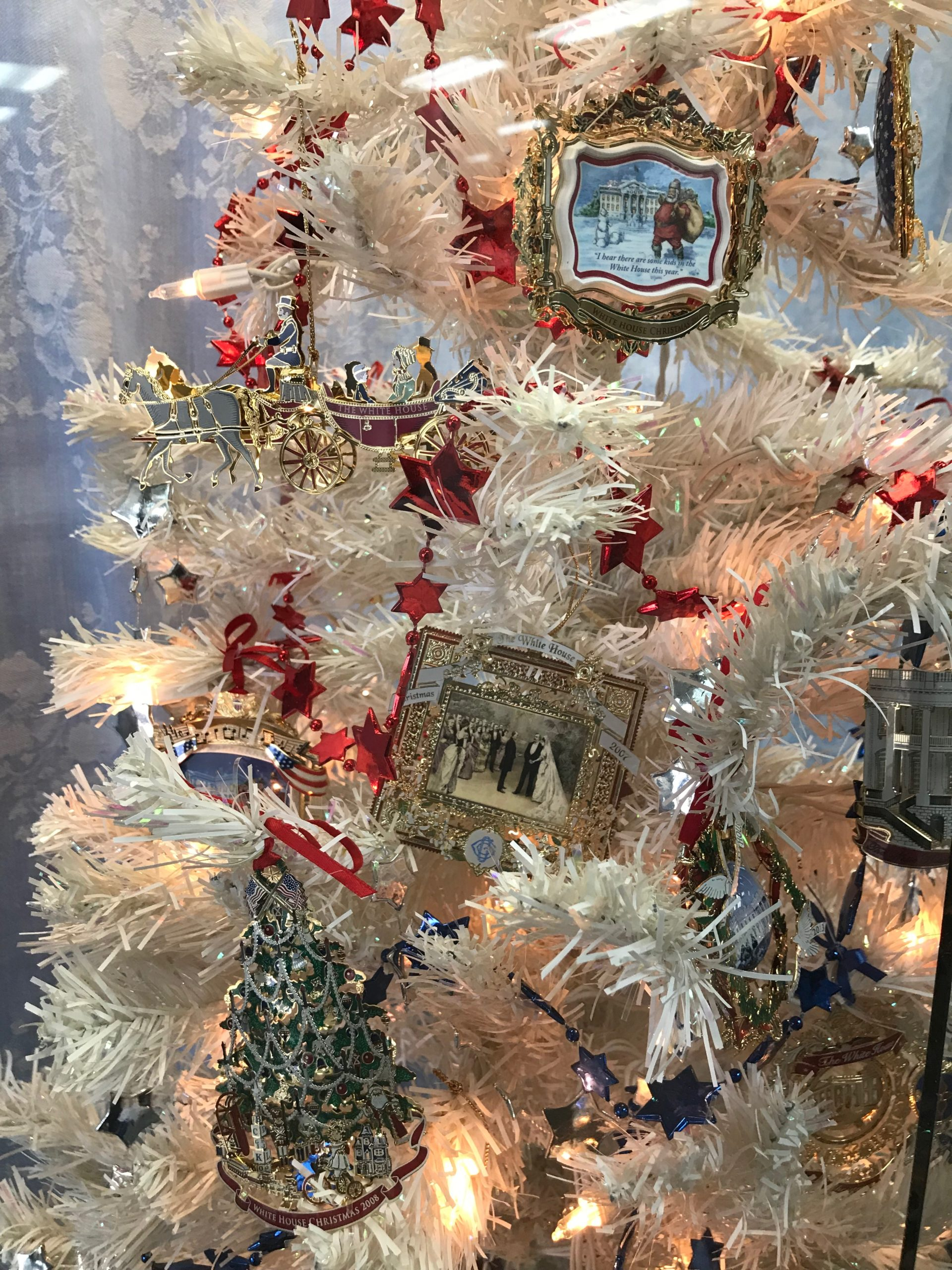 Close-up view of Christmas ornaments, including painted scenes, a wagon and a Christmas tree.