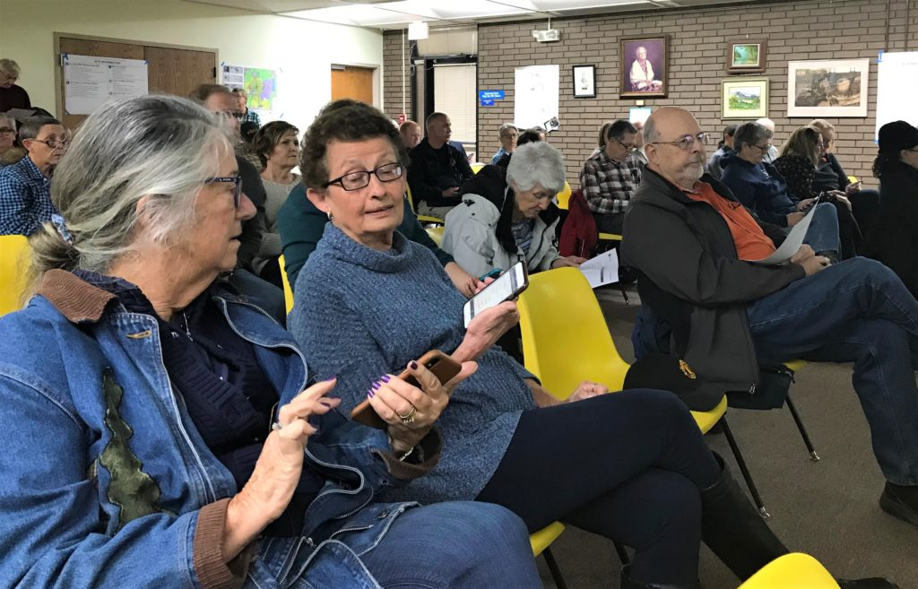 Library patrons use their smartphones to give feedback on possible library sites during one of two community meetings held Oct. 30.