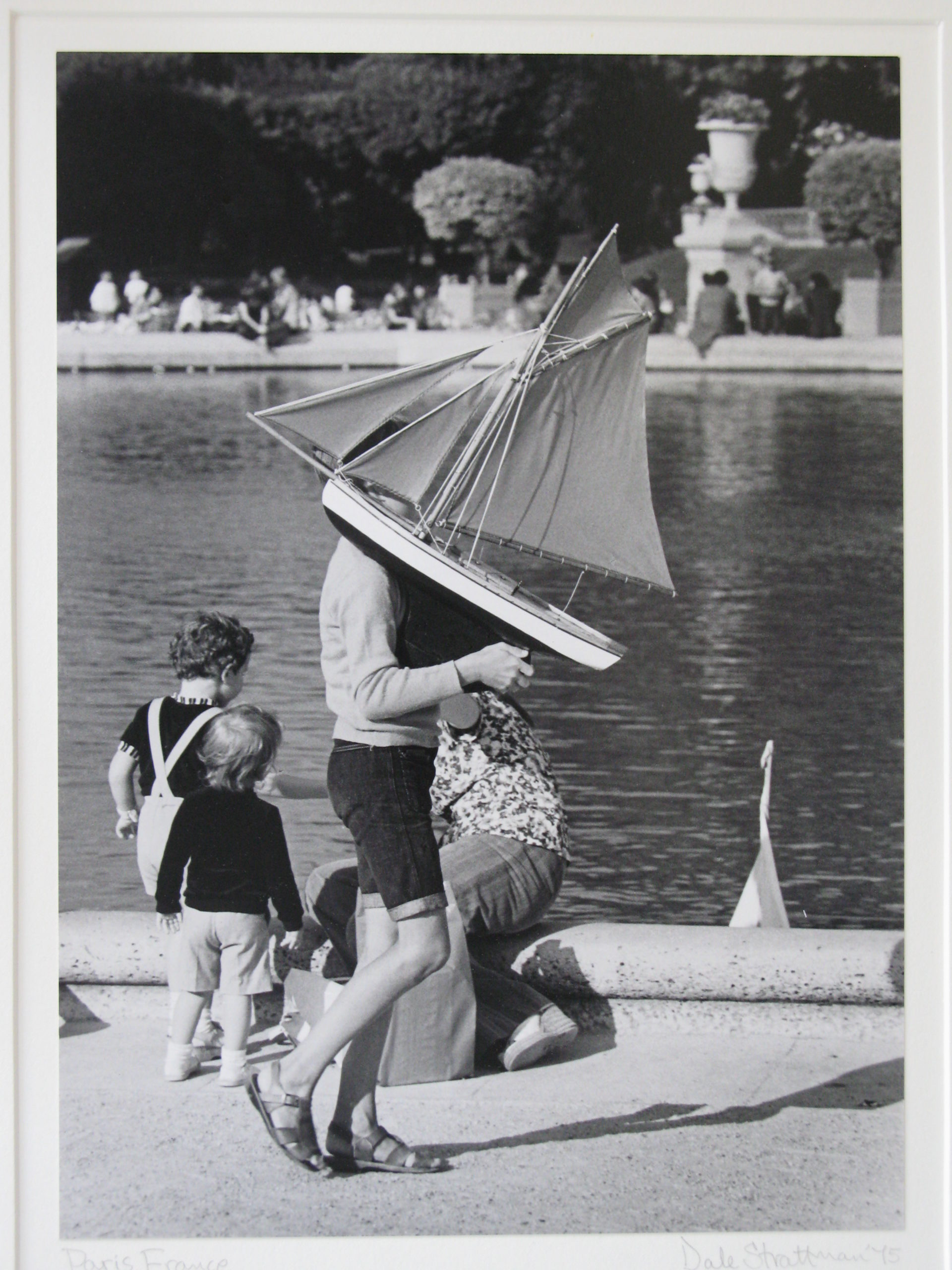 In a photo by Dale Strattman, a boy carries a toy boat in front of a reflecting pool.