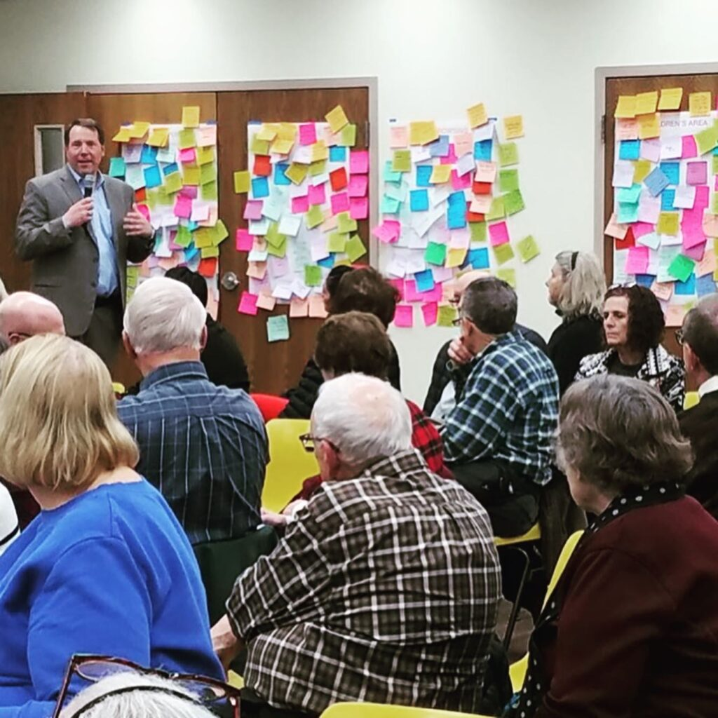 Peter Bolek speaks to attendees a community meeting held in February. Lots of sticky notes are stuck to the wall behind him.