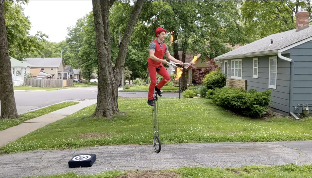 Jason D'Vaude juggles flaming torches while balanced on a four-foot-tall unicycle.