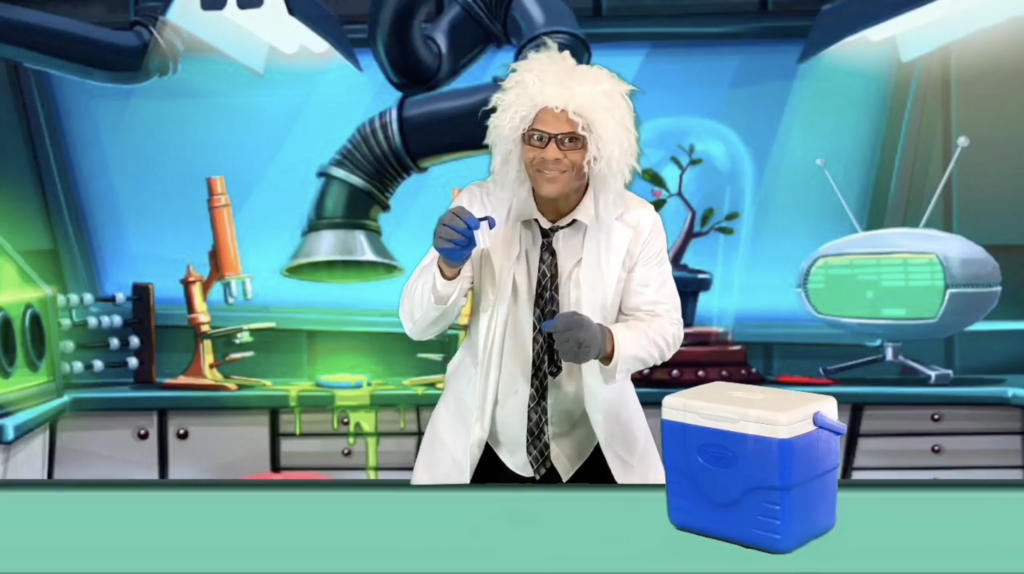 A Science Teller wears a white lab coat and white wig while standing in front of a cartoon laboratory backdrop. He holds a vial, ready to start an experiment.