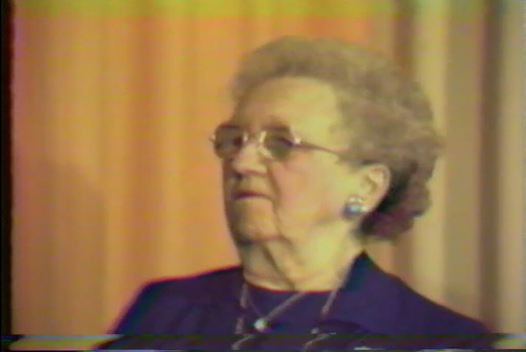 Video still capture of Irene Draper. Irene is an older woman with a gray perm, wearing glasses and opal earrings.