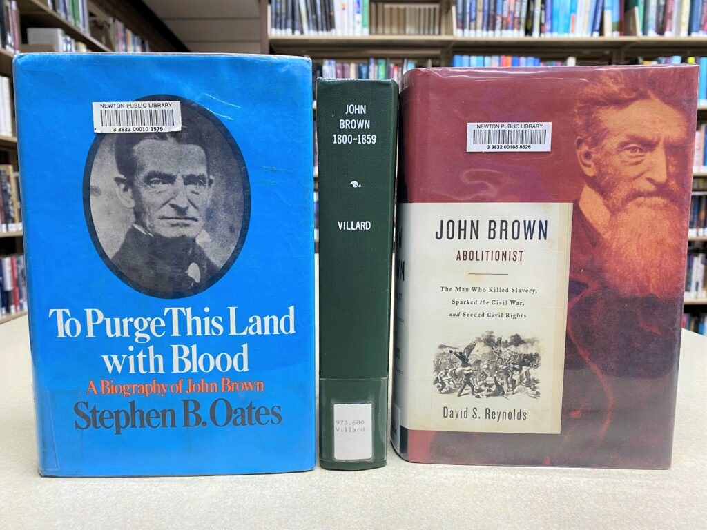 """Three library books about John Brown are displayed on a table. Titles shown are """"To Purge This Land with Blood,"""" by Stephen B. Oates, """"John Brown 1800-1859,"""" by Oswald Villard, and """"John Brown, Abolitionist,"""" by David S. Reynolds."""