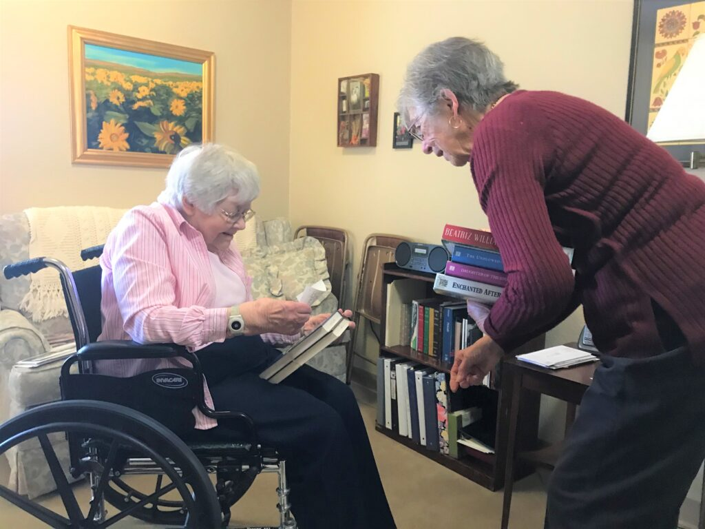 An ENLITE volunteer delivers books to an elderly library patron seated in a wheelchair inside her apartment.
