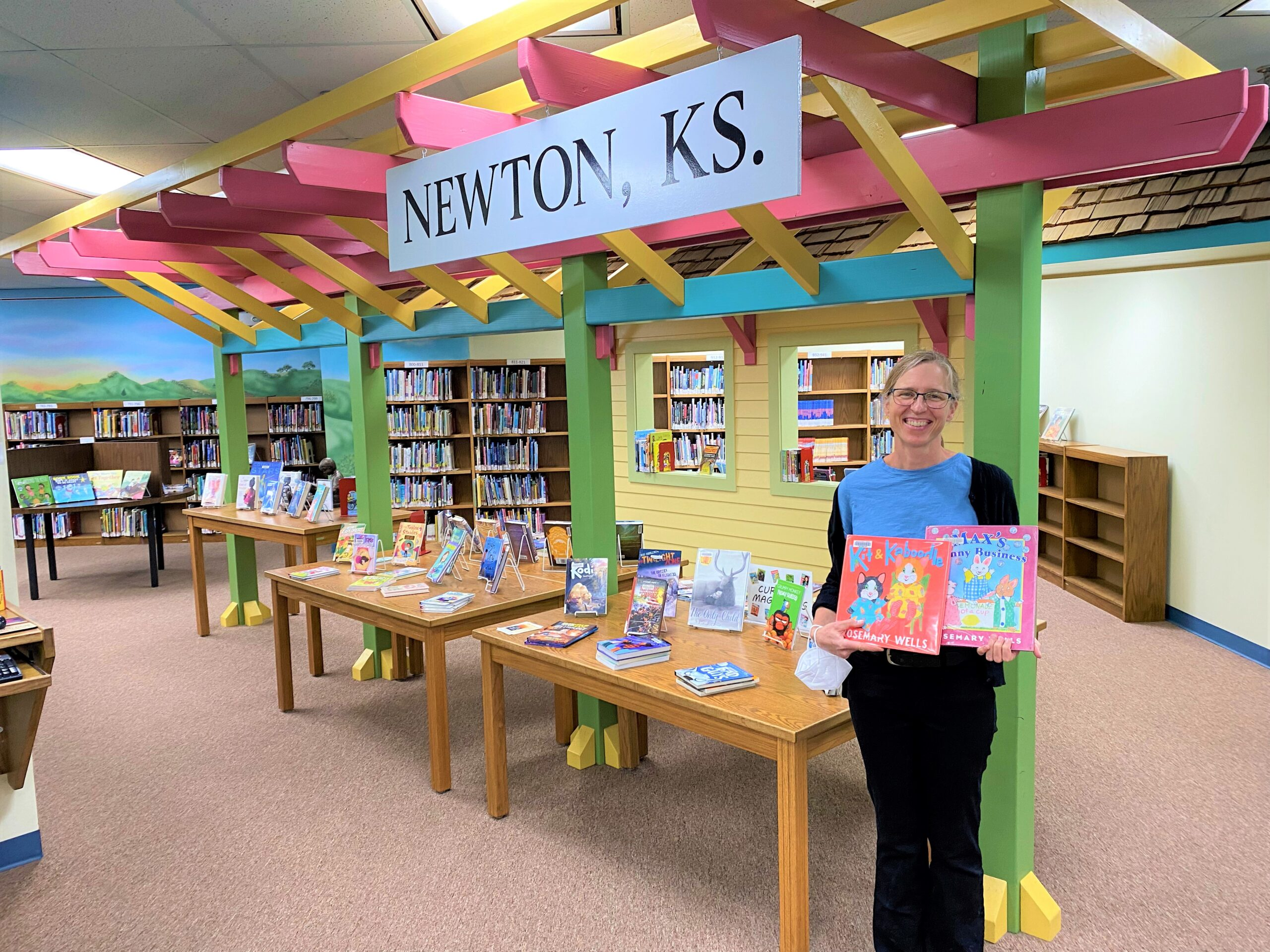 Sara Rickard poses for a photo in the children's department at Newton Public Library. She holds two children's books and stands in front of a background of bookshelves and displays.